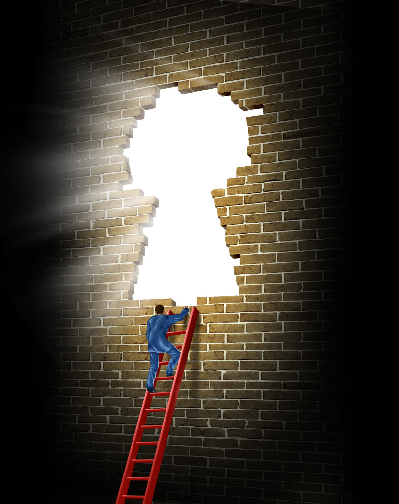 Breaking in to opportunity as a business man climbing a broken brick wall in the shape of a glowing light keyhole with a red ladder as a concept of success and winning.