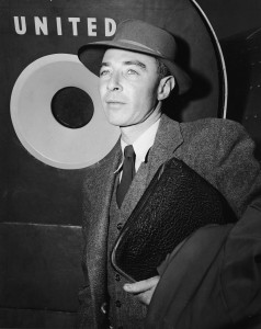 American nuclear physicist and father of the atom bomb Robert Oppenheimer (1904 - 1967), dressed in a three-piece tweed suit and hat, holds a zippered case and overcoat as he stands outside of a United Air Lines 'Mainliner 300' Douglas DC-6 airplane at LaGuardia Airport, Flushing, New York, New York, early to mid 1950s. Oppenheimer had just disembarked the airplane which had made its inaugural flight from San Francisco. (Photo by Pictorial Parade/Getty Images)